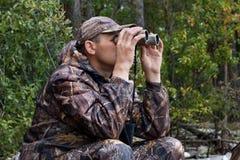 sitting hunter  looks through the binoculars Royalty Free Stock Photo