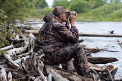 Sitting hunter  looks through the binoculars on the river Royalty Free Stock Photography