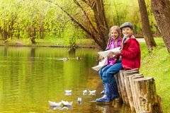 Sitting kids near the pond play with paper boats Stock Image