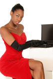 Sitting at laptop. Girl in red gown sitting at laptop in vertical format Stock Image
