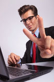 Sitting at laptop & showing victory Royalty Free Stock Photo