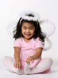 Sitting little angel. Cute little angel girl sitting on the floor stock photo