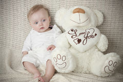 Sitting little baby in white. With  cuddle-bear Stock Image