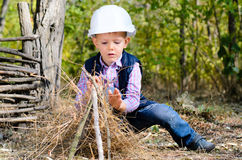 Sitting Little Boy with Helmet Playing Sticks Stock Photos