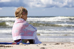 Sitting and looking. Little girl sitting on the beach and looking at the sea Royalty Free Stock Image