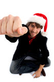 Sitting male with christmas hat and showing punch Stock Photography