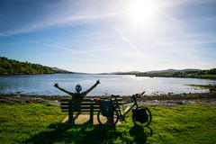 Happy man enjoying nature with bicycle. Sitting male cyclist by the lake wih his bicycle on touring trip royalty free stock photos