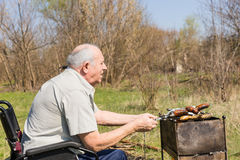 Sitting Male Elderly Preparing Food to Eat Outside Stock Images