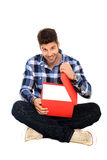 Sitting man with a box. Sitting man opens a red gift box Royalty Free Stock Photo