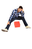Sitting man with a box. Sitting man portrait with a red gift box Royalty Free Stock Photos