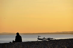 A sitting man and his bicycle on a beach at sunset Stock Photo