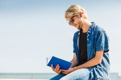Sitting man reading book outside on sunny day. Holiday, outdoor leisure time, introvert relaxation concept. Sitting hipster man wearing jeans outfit reading book Royalty Free Stock Photography