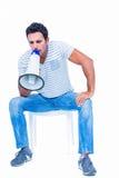Sitting man shouting through megaphone. On white background Royalty Free Stock Photos