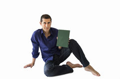 Sitting man showing a book Stock Photos