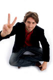 Sitting man showing peace sign Royalty Free Stock Photography