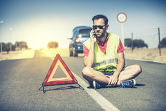 Sitting man talking by phone in the middle of the road. Royalty Free Stock Photography