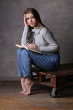 Sitting model with a book. Gray background Stock Images