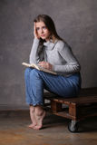 Sitting model with book touching her head. Gray background Royalty Free Stock Image