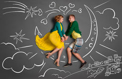 Sitting on the moon. Happy valentines love story concept of a romantic couple sitting on the moon and holding hands against chalk drawings background of a night Stock Photography
