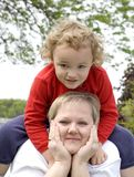 Sitting on Mother. Young boy sitting on mother while on grass plot Royalty Free Stock Image