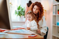 Girl sitting on knees of mother working on computer making sketches. Sitting on mother. Cute girl sitting on knees of beautiful mother working on computer making royalty free stock image