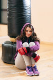 Sitting near punching bag young woman kickboxer Royalty Free Stock Photography