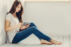 Sitting near the wall and looks in Tablet. Beautiful girl sitting near the wall and looks in Tablet Royalty Free Stock Image
