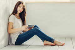 Sitting near the wall and looks in Tablet. Beautiful girl sitting near the wall and looks in Tablet Stock Photography