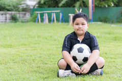 Sitting obese fat boy  soccer player with football Royalty Free Stock Image