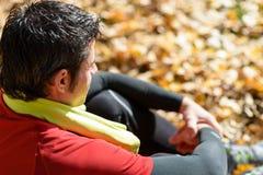 Sitting och vila för idrottsman nen Arkivfoto