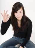 Sitting with OK sign. Young woman sitting and show the OK sign with her fingers stock photography
