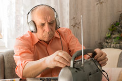 Sitting Old Man Listening News at the Radio Stock Photography