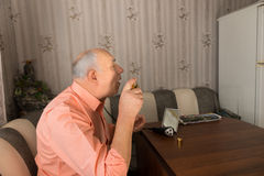 Sitting Old Man Spraying Aftershave on his Face Stock Photo