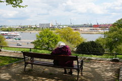 Sitting old woman. SZCZECIN, POLAND - MAY 02, 2015: Old woman sitting on a bench in front of the Odra river Royalty Free Stock Image