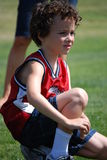 Sitting it out. Boy sitting out his turn at the side lines of a soccer field Royalty Free Stock Photo