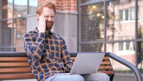 Sitting Outdoor Redhead Beard Young Man with Headache Using Laptop. 4k high quality, 4k high quality stock footage