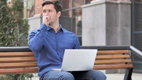 Sitting outdoor young man coughing while working on laptop. 4k high quality, 4k high quality stock video