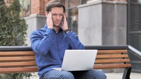 Sitting outdoor young man with headache using laptop stock footage