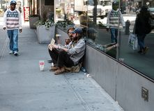Homeless couple looking for charity on the streets of New York city. stock photography
