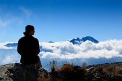 Sitting over the clouds. A woman is sitting, looking the mountain peak over the clouds Stock Photos