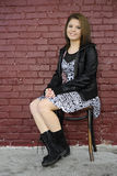 Sitting by a Painted Brick Wall Stock Photography
