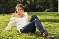 Sitting on the park. Young colombian woman dressed with white blouse and jeans pants, is sitting down on a bogota city park Royalty Free Stock Image