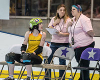 Sitting in the Penalty Box. Redding, California-February 21, 2015: A   Lava City skater sits in the penalty box and talks to officials  during a  flat track bout Royalty Free Stock Photography
