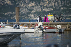 Sitting on the pier - bike rest on the lake garda. A couple in holiday at garda lake in italy (trentino Stock Photo