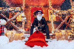Sitting on porch at christmas. Ð¡heerful punk Santa fools around near his house with a bag of gifts in his hands royalty free stock photography