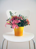 Sitting Pretty. Flower arrangement on a white chair against a light grey wall stock images
