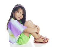 Sitting Pretty. A beautiful young girl happily looking at the viewer while sitting pretty in her shorts, multicolored shirt and sandals.  On a white background Stock Photos