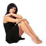 Sitting pretty brunette in black dress Stock Images