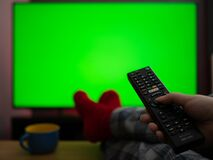 Sitting in pyjamas with feet up watching tv television with green screen chroma key