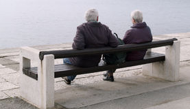 Sitting quietly. Elderly couple sitting on a bench by the sea royalty free stock image